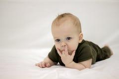 Verwirrtes Säuglingskind auf dem Bett Lizenzfreie Stockfotos