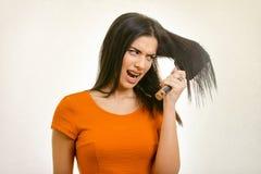 Verwirrtes unordentliches Frisurproblem Frau, die ihr schädigendes Haar bürstet lizenzfreies stockfoto