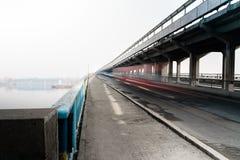 Verwischen Sie Autos auf der Brücke über dem Fluss Stockbilder