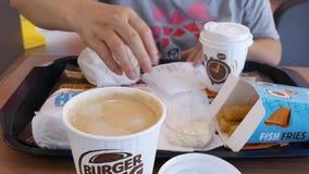 Verwischen Sie die Bewegung der Frau vorbereitend Lebensmittel an Burger King-Schnellrestaurant essend stock video