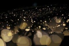 Verwischen Sie Fokus des Lichtes auf schwarzem Hintergrund von der Lampe in der Nacht auf Weihnachten vor neuem schönem romantisc Lizenzfreie Stockfotos
