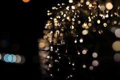 Verwischen Sie Fokus des Lichtes auf schwarzem Hintergrund von der Lampe in der Nacht auf Weihnachten vor neuem schönem romantisc Lizenzfreies Stockbild