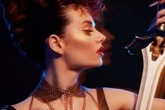 Verwischen Sie Gefühl einer Kriegersfrau, die mit einer Klinge aufwirft Lizenzfreies Stockfoto