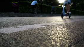 Verwischen Sie Mann auf Roller mit dem Radfahren auf Gegenseite bei Sonnenuntergang Stockbild
