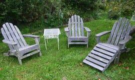 Verwitterte Adirondack-Stühle auf grünem Rasen Stockfotos