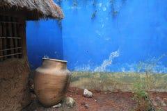 Verwitterte blaue Wand mit großem Tongefäß Stockbilder