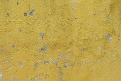 Verwitterte Gelb gemalte Betonmauer Sonnige raue Gipsfotobeschaffenheit Stockbild