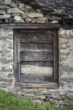 Verwitterte hölzerne Tür in einer ursprünglichen Steinhütte Stockbild