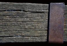 Verwitterter Holzbalken mit einer rostigen metallischen Platte Stockbilder