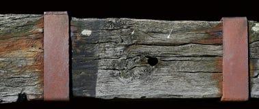 Verwitterter Holzbalken mit einer rostigen metallischen Platte Lizenzfreie Stockfotografie