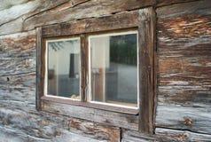 Verwittertes altes Fenster eines Holzhauses stockfoto