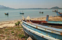 Verwittertes Fischerboot der hölzernen Weinlese auf Ufer an einer ruhigen Bucht im Meer Lizenzfreie Stockfotos