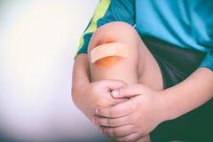 Verwond atletenkind Kindknie met een pleister en een kneuzing vin royalty-vrije stock fotografie