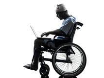 Verwonde mens in rolstoel gegevensverwerkingslaptop computersilhouet royalty-vrije stock foto