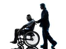Verwonde mens in rolstoel met verpleegsterssilhouet stock afbeeldingen