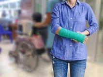 Verwonde vrouw met groen gegoten op hand en wapen bij het abstracte onduidelijke beeld h Royalty-vrije Stock Fotografie