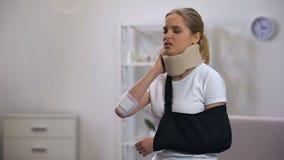 Verwonde vrouw in schuim cervicale kraag en wapenslinger die aan pijn in hals lijden rehab stock video