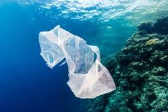 Verworfene Plastiktasche, die hinter einem tropischen Korallenriff treibt Lizenzfreie Stockfotos