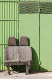 Verworpen autozetels voor een groene garagedeur stock foto