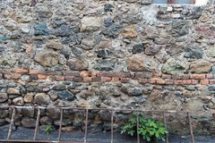Very ancient wall with stones and bricks. Old red brick and stone wall background texture with some grass in high resolution details. Very ancient wall with stock photography