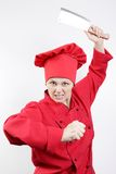 Very angry girl cook. Very angry girl the cook in a red form with a big knife a gray background stock image