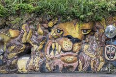 Lion graffiti on natural overgrown rock face, Barbedos. Very angry looking lion - three-dimensional - painted on escarpment - Barbados Stock Photos