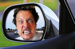 Very angry man. In a side mirror of a car Stock Photos
