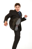 Very angry young businessman hard kicking isolated Stock Photos