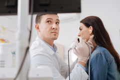 Very attentive doctor wrinkling his forehead. Detail view. Competent medical worker wearing rubber gloves looking at monitor while controlling the checkup Royalty Free Stock Photos
