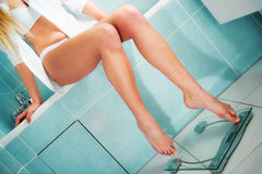 Pretty girl weighing in bathroom. Very attractive girl weighing in bathroom royalty free stock images