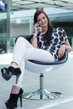 Very attractive young girl sitting on a white chair with a smart Royalty Free Stock Photography