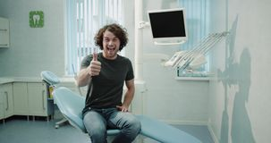 Very awesome guy with large smile visit to his dentist in a medical clinic waiting for his teeth check sitting on the. Blue dentist chair stock video