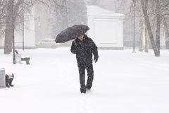 Very bad weather in a city in winter: terrible heavy snowfall and blizzard. Male pedestrian hiding from the snow under umbrella. Outdoors royalty free stock photo