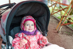 Very beautiful baby girl sitting in the pram and waiting for mom Stock Image