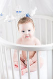 Very beautiful baby sitting in a white round crib Royalty Free Stock Photo