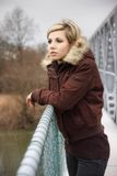 Very beautiful blonde on a bridge. Beautiful blonde in a jacket and jeans posing on a bridge, fashion photography Royalty Free Stock Images