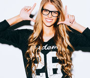 Very beautiful blonde girl hipster with long hair in fashion glasses, sniling and frame makes the thumbs. Close up. Indoor. Warm c Stock Images