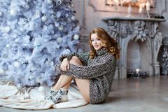 Very beautiful blonde girl in a knitted sweater and socks sittin Stock Photo