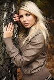 Very beautiful blonde in a nature. Portrait of a beautiful blonde in a jacket in nature, in a forest, fashion photography Royalty Free Stock Images