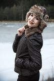 Very beautiful blonde in a nature. Portrait od beautiful blonde in a leather jacket and fur hat in a nature, next to a pond, fashion photography Stock Photography