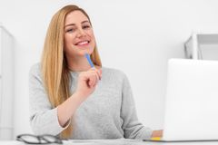 A very beautiful blonde is sitting at a table with a laptop and a pen in her hand. Young attractive woman in office or Stock Image