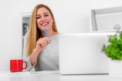 A very beautiful blonde is sitting at a table with a laptop and a pen in her hand. Young attractive woman in office or Royalty Free Stock Image