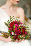 Very beautiful bouquet in red tones, which holds the girl in whi stock photo