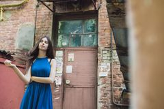 A very beautiful and cheerful girl stands on the street with long, luxurious hair stock image