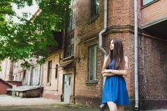 A very beautiful and cheerful girl stands on the street near a brick wall royalty free stock photo
