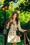 A very beautiful fashionable girl with a brown-haired hat in the. Hands of a Bengal cat, in a green park royalty free stock image