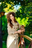 A very beautiful fashionable girl with a brown-haired hat in the. Hands of a Bengal cat, in a green park stock photography