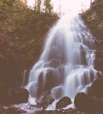 A beautiful fountain-like small waterfall in a forest. Very beautiful fountain-like small waterfall in a green forest going down round rocks into a river stock photography