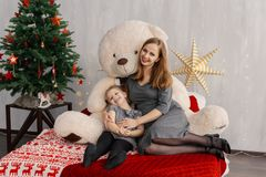 Very beautiful girl and her baby on the bed with a bear in the Christmas room. royalty free stock photography