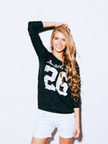 Very beautiful girl with long blond hair posing on a white background. She raised her hand above her head and smiling. Sweatshirt. And white shorts. Indoor Stock Photos